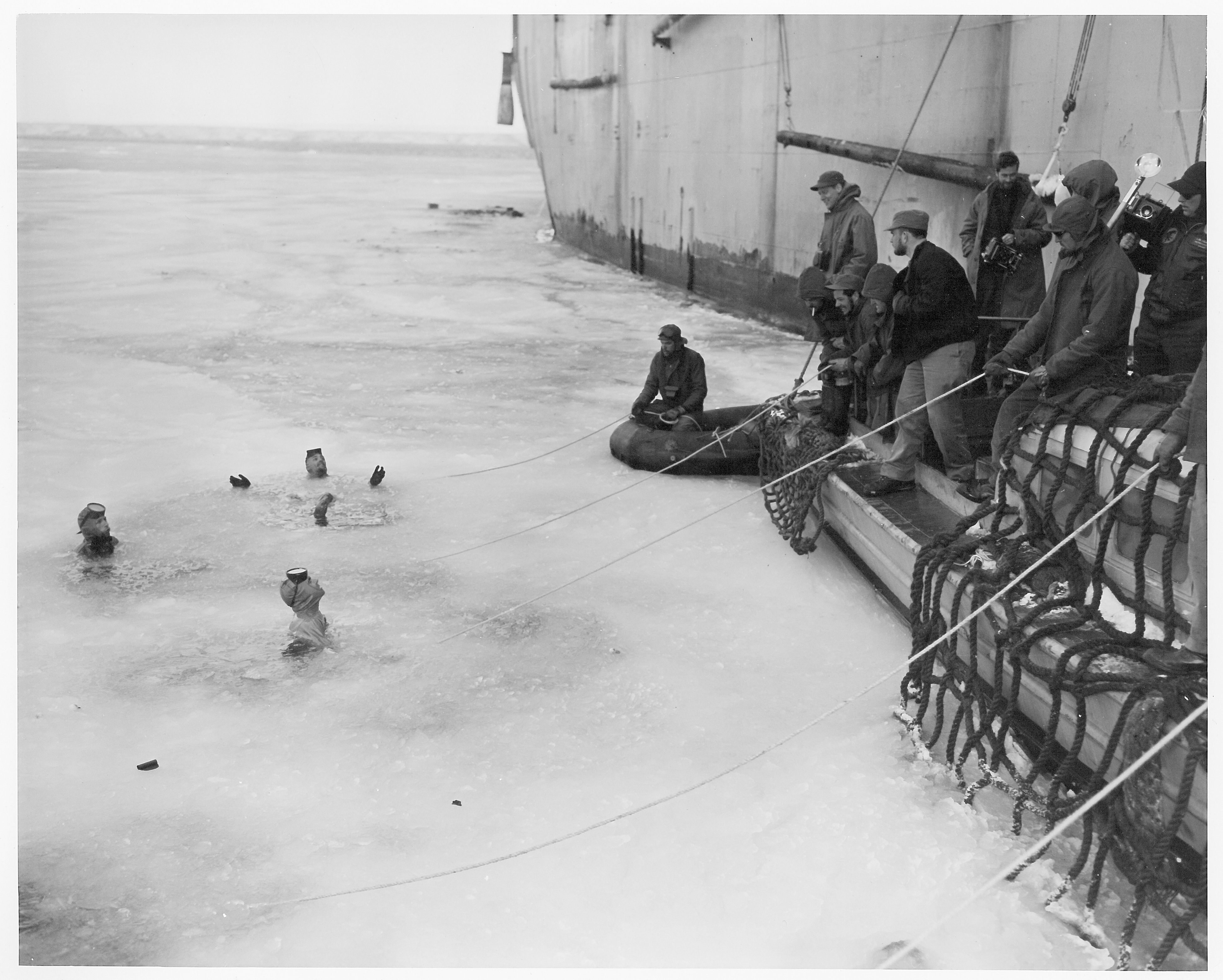 Three men swimming in icy water as several men on a boat watch.