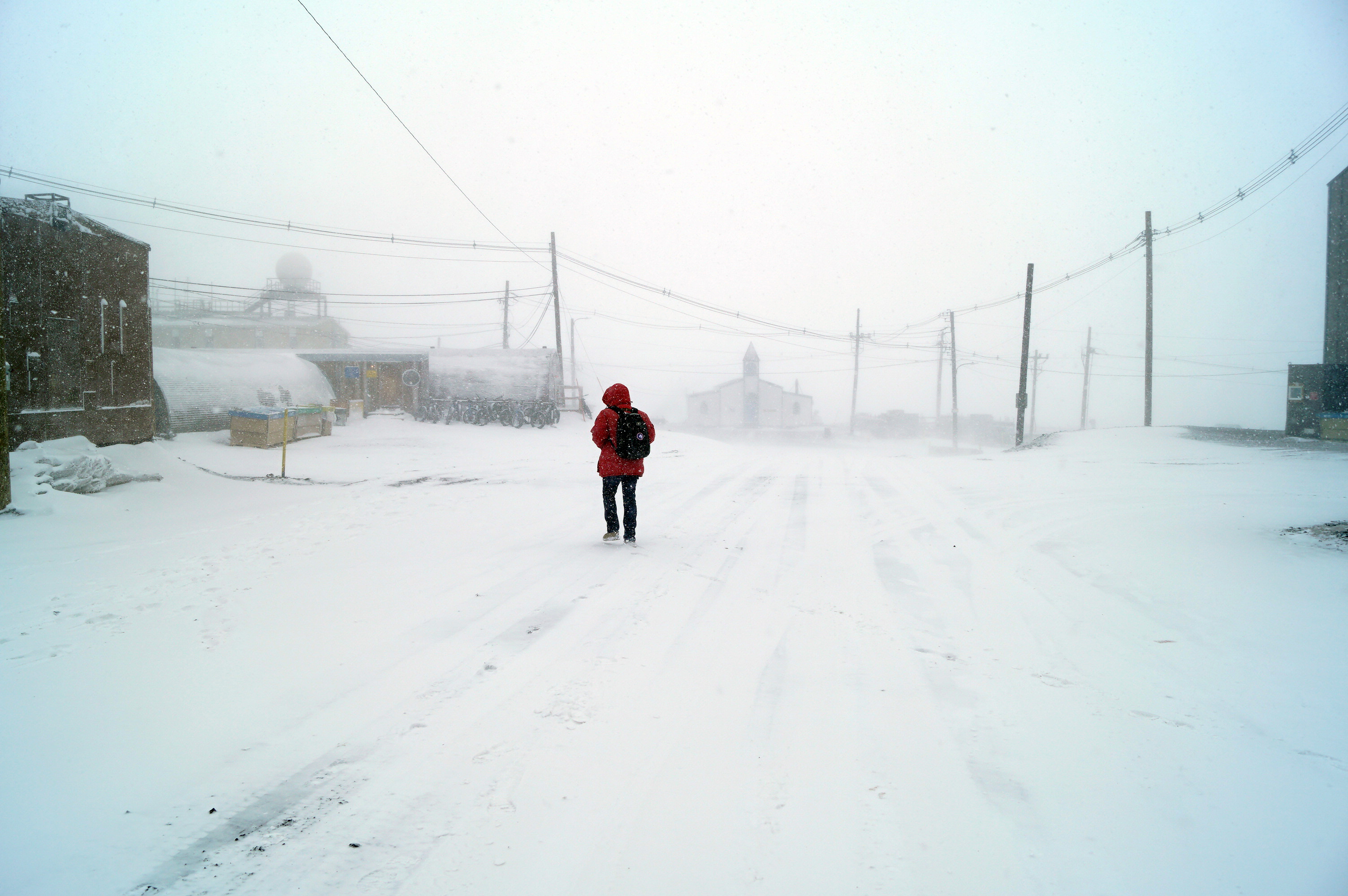 A person in a red jacket walking outside during a snow storm.