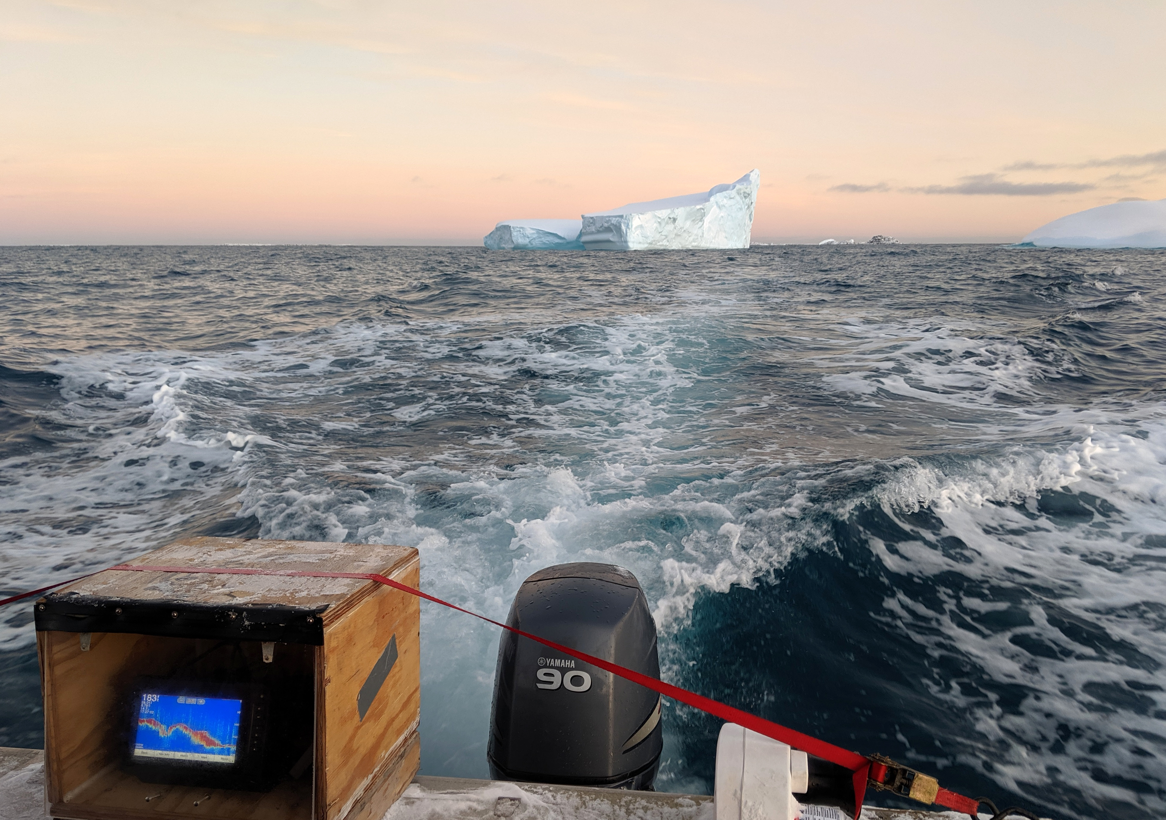 A view of a motorboat wake with an iceberg in the distance.