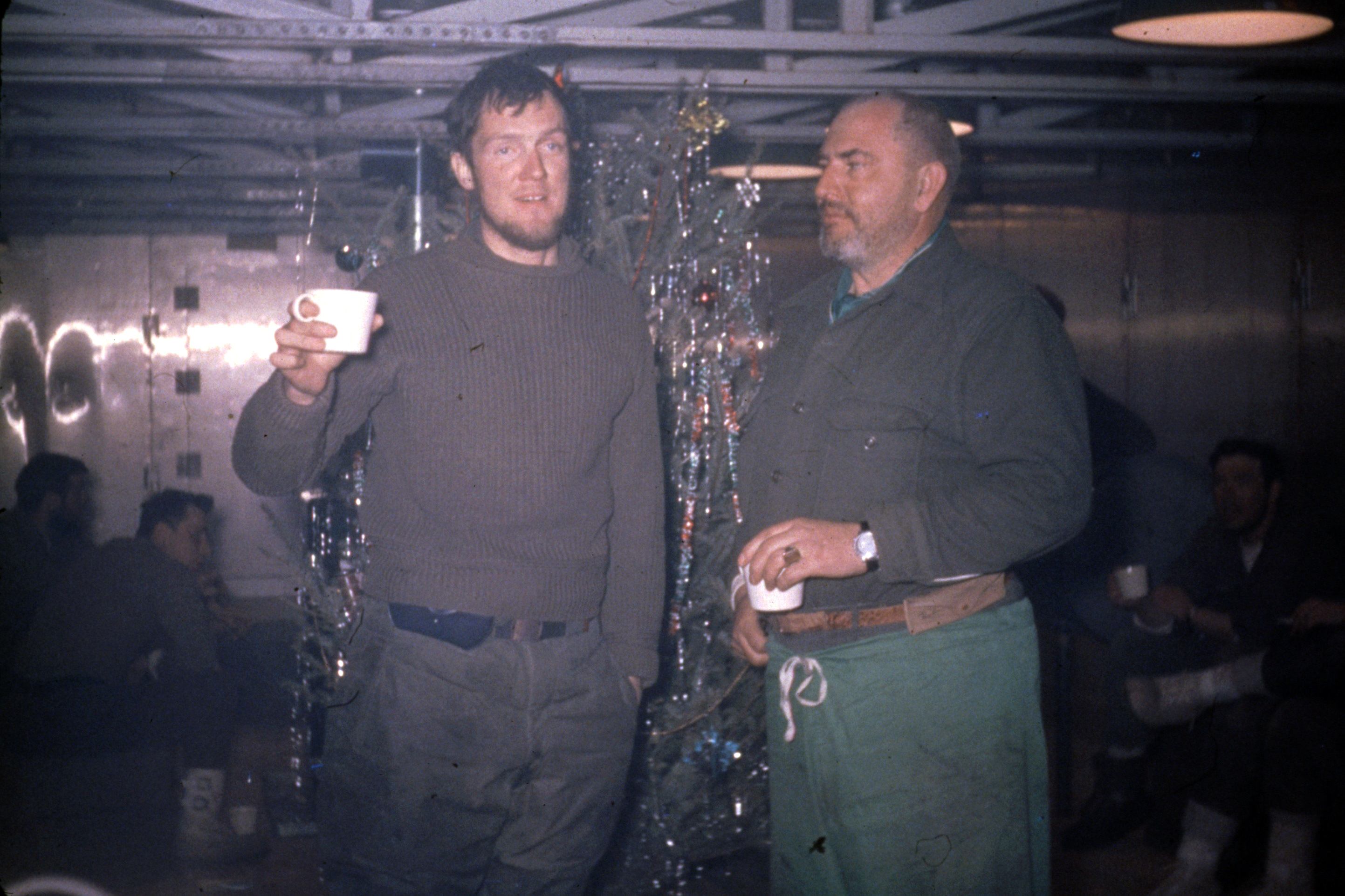 Two men share a drink in front of a Christmas tree.