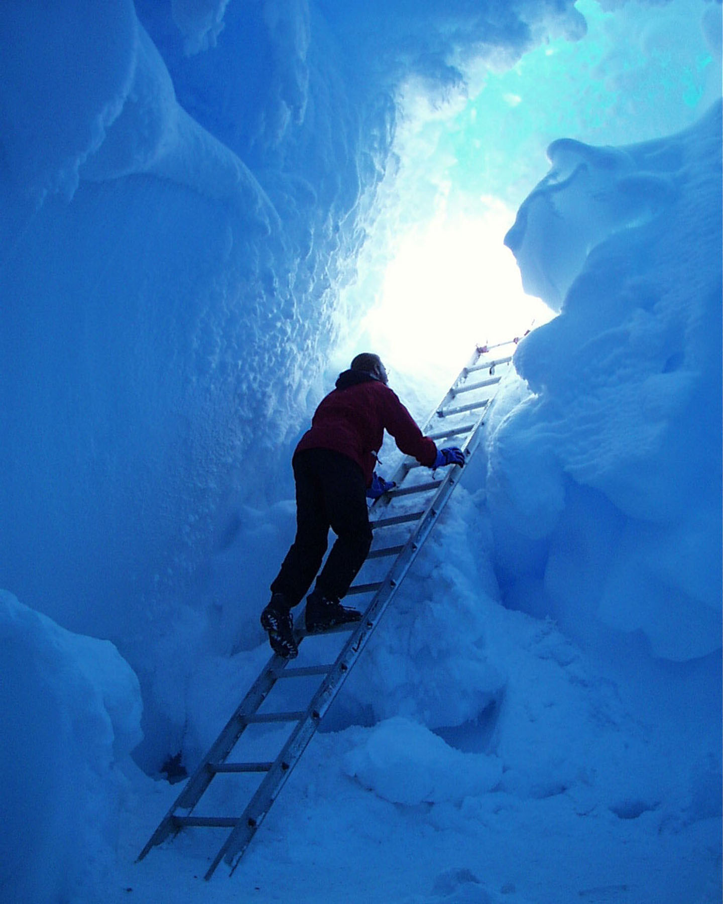 A person on a ladder in a bluish snow cave.