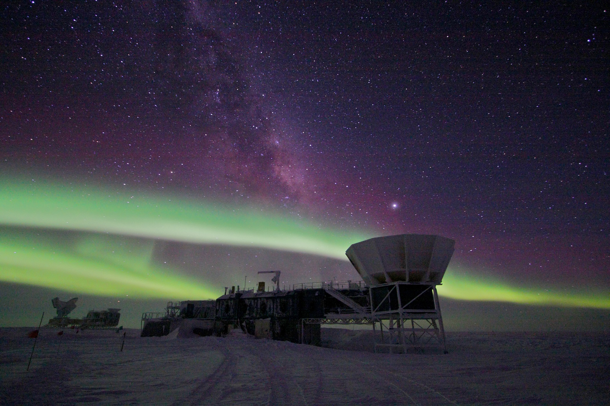 Auroras in the night sky over a science building and telescope at the U.S. research station at the geographic South Pole.