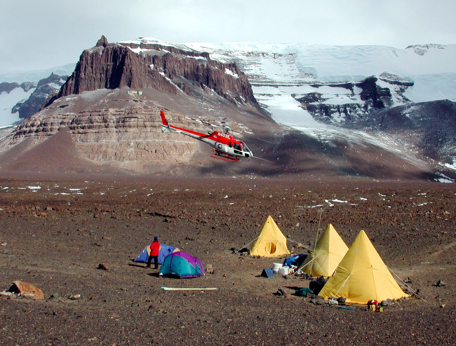 Helicopter approaches several tents on a rocky landscape.