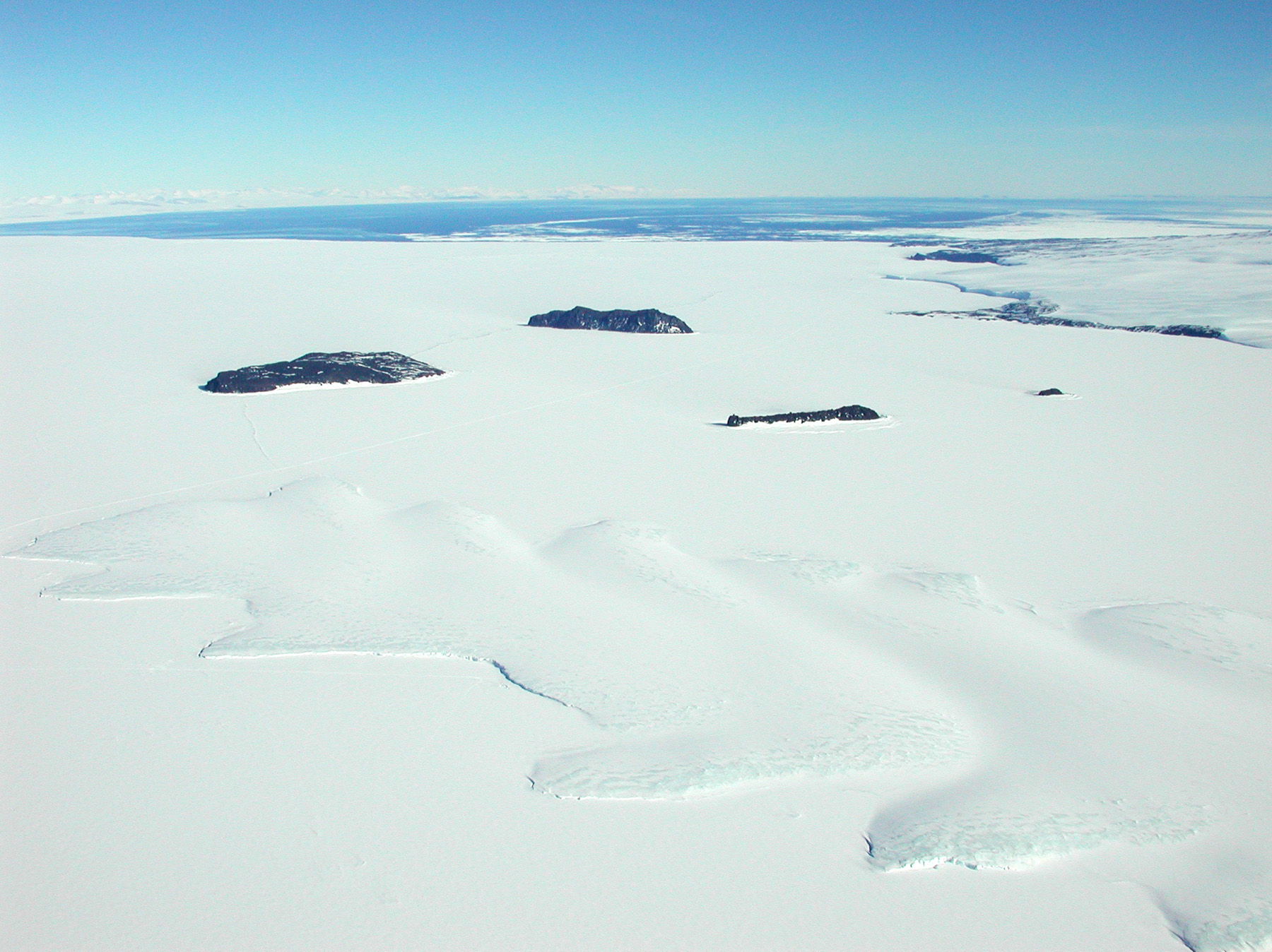 Aerial view of ice covered ocean, with small islands portruding through the ice.