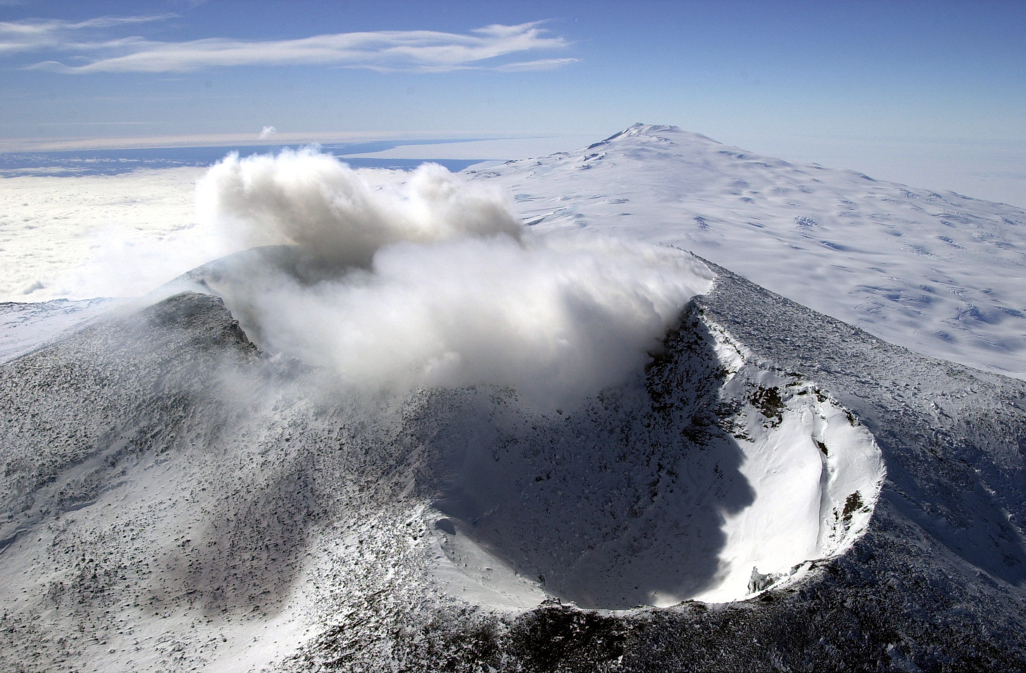 Aerial view of a volcanic cone with steam coming from it.